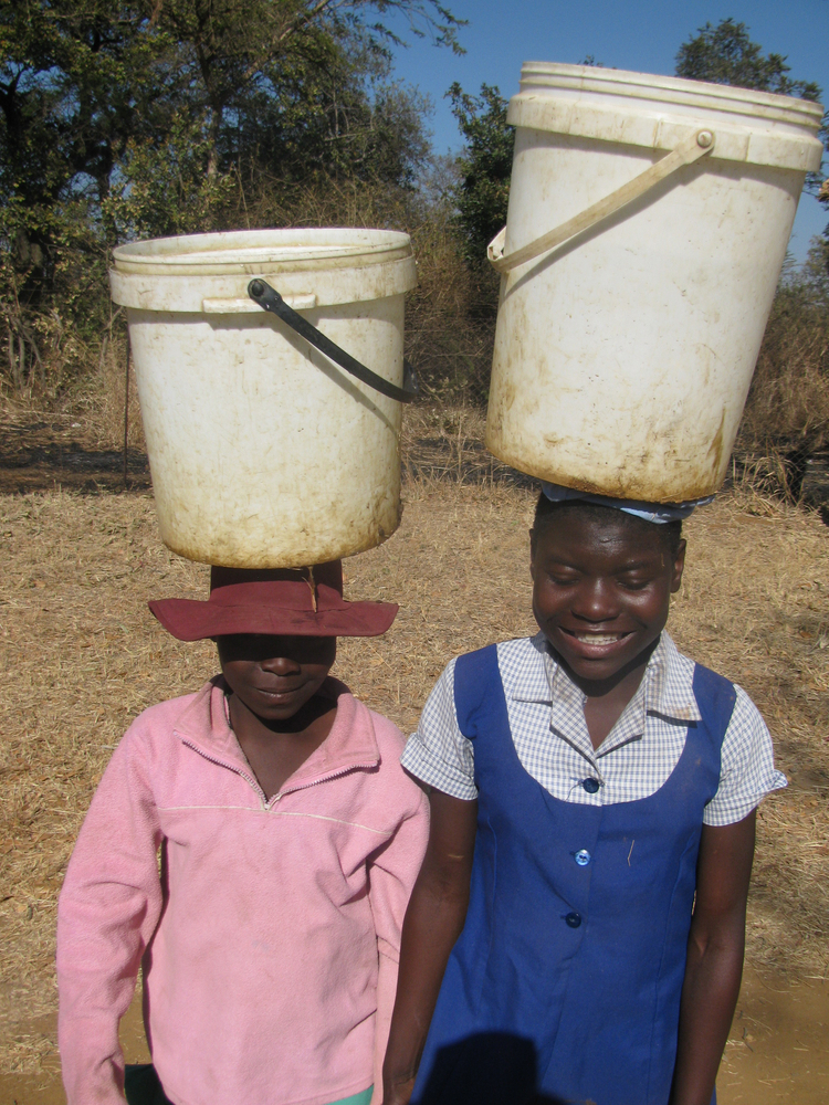 Two young women walk long distances due to the water crisis in Zimbabwe.